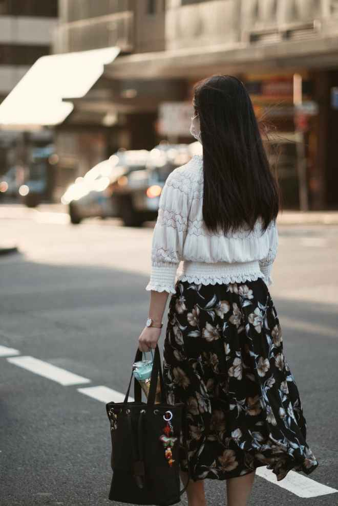woman in white long sleeve shirt and black floral skirt standing on sidewalk